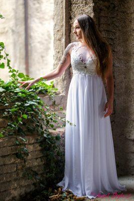 Svatební šaty Cloudine jsou stvořené pro romantickou vílu. Šaty mají šifonem podšitý živůtek, kterému dominuje šikovně řešený výstřih vykrojený do písmene V. Šifonem a krajkou jsou řešena i záda, která přilákají pohled a byla by škoda schovat je pod rozpuštěné vlasy. Sukně je lehce nařasená a krásně splývavá, při každém vašem kroku se bude neodolatelně vlnit.