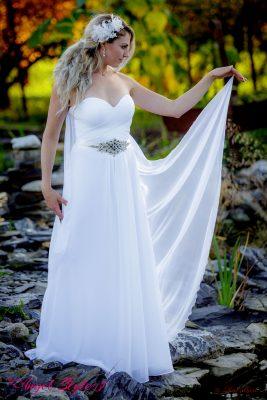 Fairy... Ve svatebních šatech Fairy se budete cítit doslova jako víla. Šaty připomínají bohémský styl, mají srdíčkový výstřih, jednoduchou splývavou sukni a dlouhou vlečku, která bude doprovázet každý váš krok. Šatům dominuje výrazná ozdoba v pase, která se krásně třpytí a šatům dodává na eleganci a přepychu.